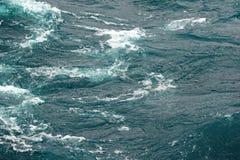 Kokande yttersida av vatten under påverkan av stark vind Färgstänk och droppar av vatten sprider i olika riktningar Arkivfoton