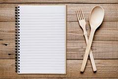 Kokbok, gaffel och sked på trätabellen royaltyfri bild