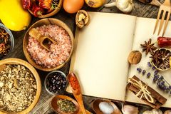 Kokbok och krydda på en trätabell kvinna för vektor för förberedelse för matillustrationkök En gammal bok i köket Recept för mat arkivfoto