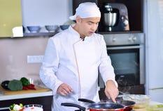 Kokchef-kok in keuken en verse groenten op lijst stock fotografie