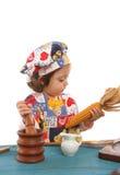 Koken van het meisje gekleed als chef-kok royalty-vrije stock afbeeldingen