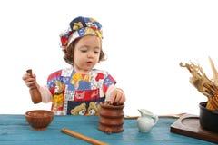 Koken van het meisje gekleed als chef-kok stock foto's