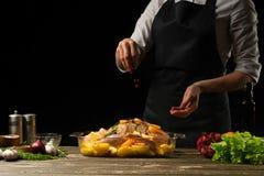 Kokend chef-kokeend bestrooi met bevroren korrels van granaatappel, horizontale foto, zwarte achtergrond royalty-vrije stock afbeeldingen