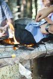 Kokend diner op kampvuur Stock Foto
