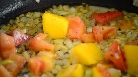 Kokend in een hete pan met mango, tomaat, aardbei en ui stock video