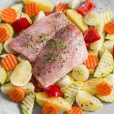 Kokend gezond voedsel - ruwe ingrediënten: aardappels, courgette, wortelen, uien, knoflook, peper en vissen overzeese baarzen Stock Afbeeldingen