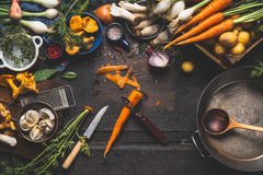 Kokend met bospaddestoelen en groenteningrediënten en keukengereedschap, voorbereiding op donkere rustieke houten lijst Stock Afbeelding