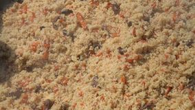 Kokend pilau in ketel en het mengen van de keukenlepel van de pilauholding Nationaal Oostelijk smakelijk voedsel stock video