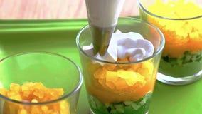 Kokend roomdessert in een glas, gelaagd met lagen vruchten en noten de kok spreidt de lagen uit stock foto's
