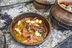 Kokend varkensvlees in een traditionele aarden pot stock afbeeldingen