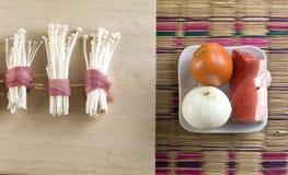 Kokend varkensvleesvlees met paddestoelen op houten lijst met tomaat en ui stock fotografie