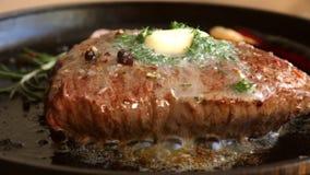 Kokend vleeslapje vlees met kruiden en botersmeltingen op bovenkant stock footage