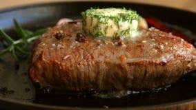 Kokend vleeslapje vlees met kruiden en botersmeltingen op bovenkant stock videobeelden