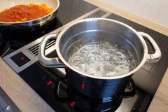 Kokend water in een kokende pot een pan op een fornuis stock foto