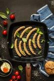Kokend - worsten op een grill pan, zwarte achtergrond Royalty-vrije Stock Afbeeldingen
