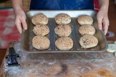 Kokende broodjes met sesamzaden Bak zoete broodjes van deeg op protvin royalty-vrije stock afbeeldingen