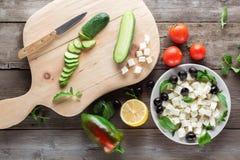 Kokende Griekse salade, die een komkommer snijden Royalty-vrije Stock Foto's