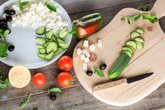 Kokende Griekse salade, die een komkommer snijden Royalty-vrije Stock Foto