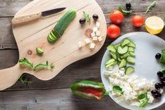 Kokende Griekse salade, die een komkommer snijden Stock Afbeelding