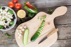 Kokende Griekse salade, die een komkommer snijden Stock Afbeeldingen