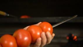 Kokende groenten op een open brand Picknick op de lucht, voedsel, plezier Tomaten op brandclose-up stock video