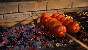 Kokende groenten op een open brand Picknick op de lucht, voedsel, plezier Tomaten op brandclose-up stock footage