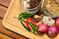 Kokende ingrediënten Kruid en kruiden met ui en knoflook op houten raad royalty-vrije stock afbeeldingen