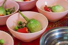 Kokende klasse: Thai, erwtenaubergines, rode Spaanse pepers in kommen Stock Afbeeldingen
