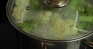 Kokende kleurrijke broccoli en bloemkool in de pan met kokend water stock footage