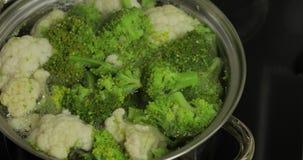 Kokende kleurrijke broccoli en bloemkool in de pan met kokend water stock videobeelden