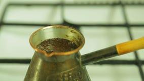 Kokende koffie in de Turk op het fornuis stock video