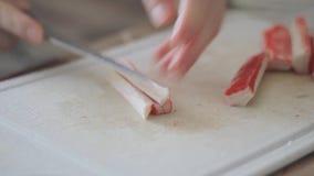 Kokende Krabsalade De vrouwelijke hand snijdt de stokken van de ingrediëntenkrab met een mes op de raad De vakantie komt spoedig stock videobeelden