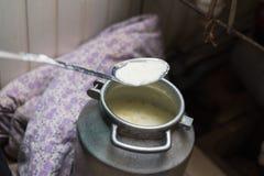 Kokende kwark en kaas thuis De mens creeert kaas, het verwarmen melk en wei in een aluminiumpan stock foto's