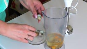 Kokende mayonaise Een vrouw voegt kwartelseieren in een mixerkom toe stock video