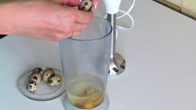 Kokende mayonaise Een vrouw voegt kwartelseieren in een mixerkom toe stock videobeelden