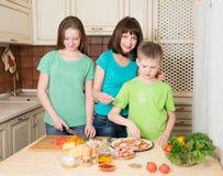 Kokende pizza thuis Het vullen van eigengemaakte pizza met ingrediënten stock fotografie