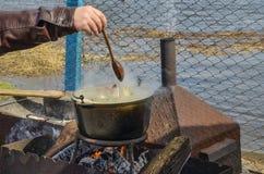 Kokende soep op de aard in een ketel stock foto's
