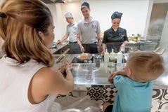 Kokende team en chef-kok die voedsel maken bij open keuken voor kinderen en families binnen restaurant stock afbeelding