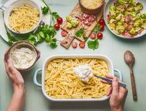 Kokende voorbereiding van de Amerikaanse deegwaren van de stijl hartelijke macaroni in kaasachtige saus Vrouwelijke hand die deeg stock fotografie