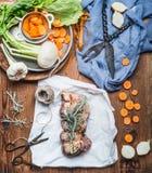 Kokende voorbereiding van ruw vleesbraadstuk met groenten en verse specerij op rustieke houten achtergrond, hoogste mening stock foto's