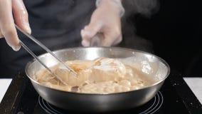 Kokende zeevruchten Gezond voedselconcept Professionele chef-kok in handschoenen die kammosselen koken die hen draaien met culnar stock video