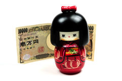 Kokeshi doll and japanese currency Royalty Free Stock Photos