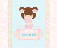 Kokeshi doll on the pink background with floral o Royalty Free Stock Photos