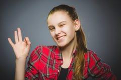 Koket meisje die O.k. tonen De tiener van het close-upportret glimlachen geïsoleerd op grijs royalty-vrije stock afbeeldingen