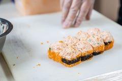 Kokhanden die Japans sushibroodje maken Japanse chef-kok die op het werk heerlijk sushibroodje met paling en avocado voorbereiden stock foto