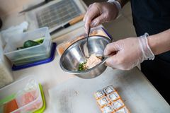 Kokhanden die Japans sushibroodje maken Japanse chef-kok die op het werk heerlijk sushibroodje met paling en avocado voorbereiden stock foto's