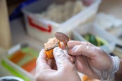 Kokhanden die Japans sushibroodje maken Japanse chef-kok die op het werk heerlijk sushibroodje met paling en avocado voorbereiden royalty-vrije stock foto's