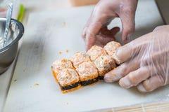 Kokhanden die Japans sushibroodje maken Japanse chef-kok die op het werk heerlijk sushibroodje met paling en avocado voorbereiden stock afbeelding