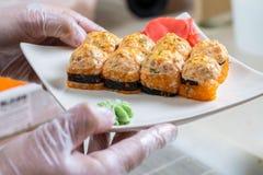 Kokhanden die Japans sushibroodje maken Japanse chef-kok die op het werk heerlijk sushibroodje met paling en avocado voorbereiden royalty-vrije stock fotografie