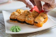 Kokhanden die Japans sushibroodje maken Japanse chef-kok die op het werk heerlijk sushibroodje met paling en avocado voorbereiden royalty-vrije stock foto